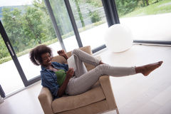 African american woman at home in chair with tablet and head pho Royalty Free Stock Image