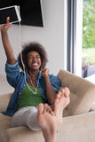 African american woman at home in chair with tablet and head pho Stock Photos