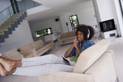 African american woman at home in chair with tablet and head pho Royalty Free Stock Photo