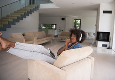 African american woman at home in chair with tablet and head pho Stock Image