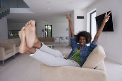 African american woman at home in chair with tablet and head pho Royalty Free Stock Photos