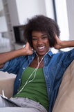 African american woman at home in chair with tablet and head pho Stock Photography