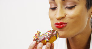 African American woman indulging in a donut Stock Photography