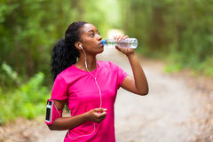 African american woman jogger drinking water - Fitness, people royalty free stock photography