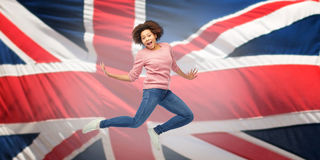 African american woman jumping over english flag Royalty Free Stock Photography