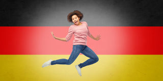 African american woman jumping over german flag Stock Images