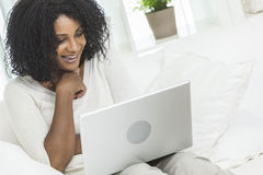 African American Woman, Laptop Computer at Home. Beautiful smiling African American woman at home sitting on sofa or settee using her laptop computer Stock Photo