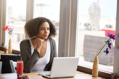 African american woman with laptop looking out of window Royalty Free Stock Photography