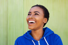 African american woman laughing against green background Stock Photos