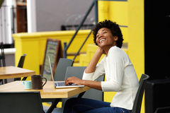 African american woman laughing with laptop at cafe Stock Photo