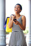 African american woman laughing with phone and shopping bags Royalty Free Stock Photography