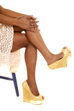 African American woman legs heels sitting. An African American woman showing off her legs and fun shoes Royalty Free Stock Image
