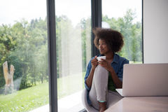 African American woman in the living room. Young african american woman smiling sitting near bright window while looking at open laptop computer on table and Royalty Free Stock Photo