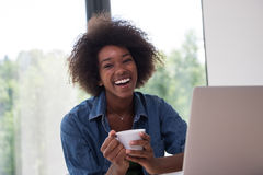 African American woman in the living room. Young african american woman smiling sitting near bright window while looking at open laptop computer on table and Royalty Free Stock Images