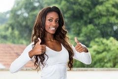 African american woman with long hair showing both thumbs up. Outdoors in the summer royalty free stock photos