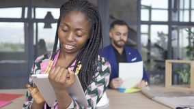 African American woman looking pictures on tablet in the foreground while male designer checking papers in the. African American woman looking pictures on her stock video footage