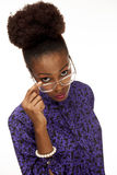 African American woman looks over her glasses at you. An African America woman looks over the top of her glasses with a very displeased look stock photography