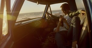 Woman lying on mans lap in a pickup truck at beach 4k stock footage