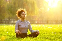 African american woman meditating in nature. Young african american woman meditating in nature Stock Photography