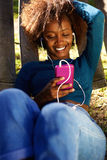 African american woman with mobile phone and earphones Royalty Free Stock Photo