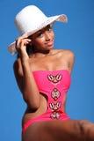 African american woman in monokini and sun hat. Beautiful young african american woman with happy smile wearing pink monokini swimsuit and sun hat sitting in Stock Photos