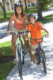 African American Woman Mother Boy Son Riding Bike. A young African American women & boy child, mother & son, riding bicycles in the summer Stock Photo
