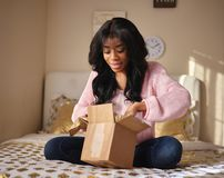 African american woman opening box on bed royalty free stock images