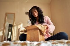 African american woman opening box on bed stock image