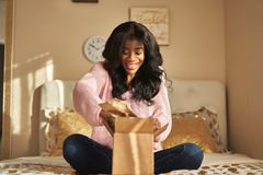African american woman opening box on bed royalty free stock photo