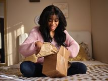 African american woman opening box on bed stock images
