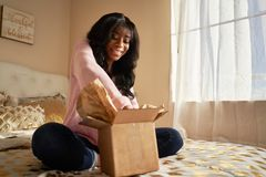 African american woman opening box on bed royalty free stock photos
