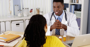 African American woman patient speaking with doctor at office desk Stock Photo