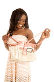 African American woman peach dress purse open look down. An African American looking down into her bag with a smile Royalty Free Stock Photography