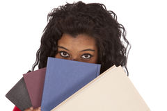 African American woman peaking from behind books. An African American woman is peaking out from behind a stack of books Stock Photo