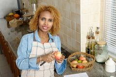 African american woman peeling apples, in the kitchen Stock Photo