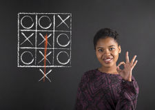 African American woman with perfect hand signal with a tic tac toe diagram on blackboard background Stock Photos