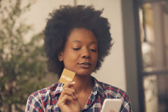 African american woman with phone and credit card Royalty Free Stock Images