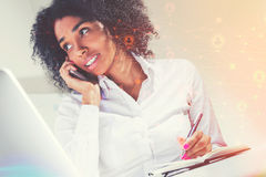 African American woman on phone, network. Portrait of an African American businesswoman talking on a smartphone in office. Network sketch in the foreground stock image