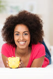 African American woman with a piggy bank Royalty Free Stock Photography