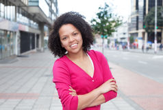 African american woman in pink shirt with crossed arms in the city Stock Image
