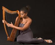 African-American woman playing with harp. Black music : Portrait of young beautiful Afro American woman with harp Royalty Free Stock Photo