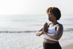 African American woman practicing yoga at the beach stock photos