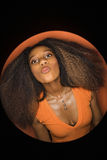 African-American woman puckering lips. Vignette of young African-American adult woman with big hair and low cut dress on orange background puckering her lips Stock Photos