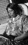African American woman reading. A black and white view of an African American woman sitting in a caned rocking chair, reading stock photography
