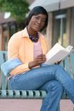 African American Woman Reading a Book Outdoors. African American Woman reading a book on a bench outdoors in a city setting Royalty Free Stock Photography