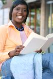 African American Woman Reading a Book Outdoors. African American Woman reading a book on a bench outdoors in a city setting Stock Photo