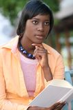 African American Woman Reading a Book Outdoors. African American Woman reading a book on a bench outdoors in a city setting Royalty Free Stock Images