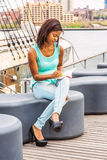 African American Woman reading book by river in New York. African American Woman wearing green tank top, blue fashionable jeans, sitting on deck at harbor Stock Photos