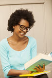 African american woman reading with glasses. Happy african american woman reading book Stock Image