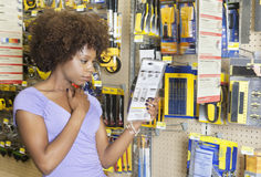 African American woman reading instructions on a product at super market Royalty Free Stock Photo